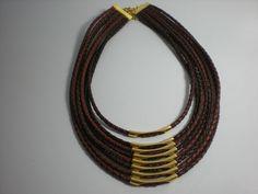 colar feito de couro marrom com oito voltas e acabamento com alongador em corrente dourada.
