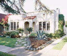 Spanish style bungalow. paved path in grass with succulent planters - ideas for Spanish casita.