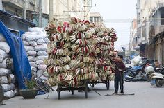 a worker hauls phone casings on a tricycle.  // china's electronic waste village.