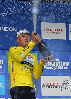 Overall tour winner Britain's Steve Cummings riding for Dimension Data celebrates with champagne on the podium in his leader's yellow jersey after...