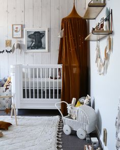 Gender neutral nursery room. Gold mustard canopy with wood look wall paper. Woodlands meets bohemian theme @misskyreeloves