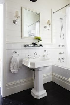 Classic white bathroom design with tongue and groove panels paired with large subway tile backsplash framing ivory beveled mirror flanked by single sconces with pleated shades and vintage glass shelf over pedestal sink.