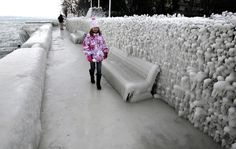A boy sits in front of an ice covered car in Versoix, near Geneva, Switzerland, on February 5, 2012