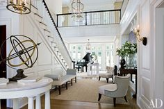 Designer Thomas Pheasant added a bay to brighten a Virginia home's entrance hall, where Luis Montoya and Leslie Ortiz's Two Plums is displayed with a pair of armillary spheres; Pheasant designed the chairs for Baker.