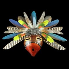 """Exotic Feather Gourd Mask by D.R. Nance Width: 18 """" Height: 14 1/2 """" Depth: 3 1/2 """" Medium: Natural Gourd, Paint, Natural Parrot, Guinea Fowl, and Exotic Fowl Feathers, Leather Tribe: Lumbee"""