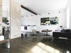 love the exposed structural elements..ceiling beam, masonry...and the acid stained concrete floors