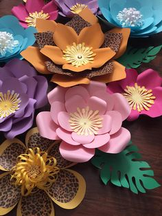 Handmade paper flower sets Made for birthdays, decorations , or any event. Made to order. 10 piece paper flower set Flowers ranging from 6-14. Set includes 1 large flower, 3 medium flowers, 4 small flowers, and 2 extra small flowers. Flowers have a hook attached to the back of