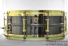 Ludwig Black Beauty Snare Drum w/ Brass Trim 5x14  Features black nickel plated seamless brass shell, brass plated tube lugs & die cast hoops, brass P86 throwoff, Monroe Keystone Badge; model # LB416BT.  Purchase Here: http://www.drumcenternh.com/drums/snare-drums/5x14-black-beauty-w-brass-trim.html
