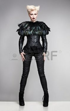 futuristic fashion model wearing leather clothes and a blouse made of feathers standing on a white platform and posing Stock Photo - 18617522