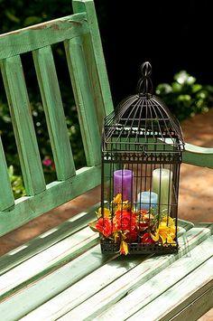 Na gaiola, que virou objeto de decoração no jardim, velas coloridas e flores artificiais, que não murcham ao sol. A ideia é de Claudia Pixu