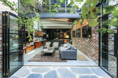 Sam Crawford Architects have transformed what was once a commercial garage sandwiched between terrace houses, into a bright and modern home that's long and narrow, and features a material palette of black steel, recycled brick, concrete and timber.