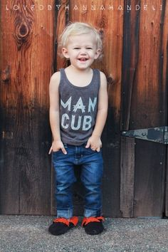 """Man Cub""Making its return Spring/Summer 2014Please note that this tank runs SMALL. Printed with ultra soft water based white ink on American Apparel's Kids Tri-Blend tank in color Tri-Coffee.(Tri-Blend (50% Polyester / 25% Cotton / 25% Rayon) construction)"