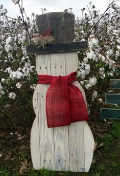 Snowman made from reclaimed pallet wood. He has a red bird nesting on his hat brim. He wears a burlap scarf. You can choose red or natural. A wire