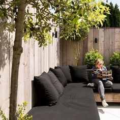 a wooden corner sofa with black cushions and pillows