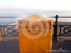 Smoke coming from orange BBQ charcoal waste bin on beach of Hove seafront.