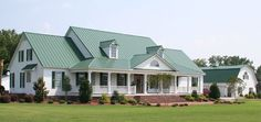 Green metal roof/white house/green shutters/white porch with matching barn