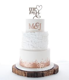 White & copper. Rustic yet classy. This wedding cake has it all. Rustic ruffles, copper sequins and presented on a lovely rustic timber slab! Cake was lemon butter cake on the top and red velvet on the base.
