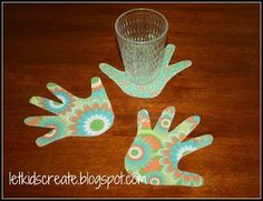 """To make them I traced my daughter's handprint onto a sheet of cardstock and cut it out for a template.  We traced four handprints from each girl onto a piece of scrap fabric using chalk.  I trimmed the fabric so that it would fit nicely onto my sheet of Stiff Fusible Interfacing.  Then I placed another piece of coordinating fabric on the underside of the interfacing.  I ran a hot iron (of course this is an adult's job) over the fabric and interfacing """"sandwich"""" for roughly 30 seconds or so."""