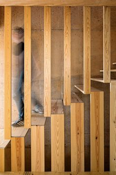 Paratelier designed this linear staircase with vertical wooden boards that connect the treads to the ceiling above and the floor below.