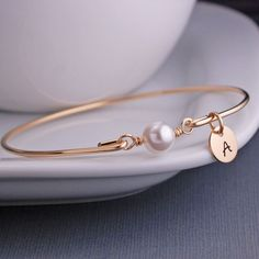 An 8mm white Swarovski pearl is the center of this bangle bracelets. Each bangle is made of heavy gauge, 14k gold filled wire, hand-hammered and tumbled for shine and strength. *ALL charms are optional. There is an option to add a personalized initial charm as shown in the first picture, or any other engraved charm as shown in the last photo. Please let me know the charm you want in the notes to seller section at checkout. ********** The bracelets are bangle style and slip over the hand…