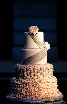 Romantic ruffle cake complete with silver sash, sugar flowers, and a touch of rhinestone sparkle bands.