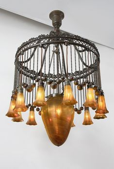 "Tiffany Studios ""Moorish"" Chandelier  A Tiffany Studios New York glass and bronze ""Moorish"" chandelier, featuring a central golden iridescent Favrile glass ""Stalactite"" surrounded by twelve golden iridescent Favrile glass ""Lily"" shades hanging from a patinated bronze crown with alternating ball and chain decoration"