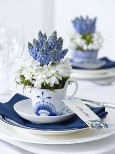 Mooie decoratie tafel voor Pasen. Oude kopjes met bloemen erin. DIY