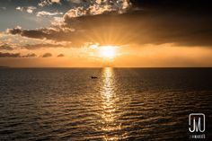Sailing in Sunset. A boat is sailing away in front of sunset on calm sea. Connect with me at http://jimmakos.com/photography