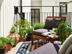 Terrazas de entretiempo con un toque masculino. Muebles de madera, colores neutros y una alfombra de tejido étnico.