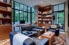 Lots of natural greenery to contrast with the wood interior.  Books and big chairs.  A calm and restful room with a spare masculine feel.