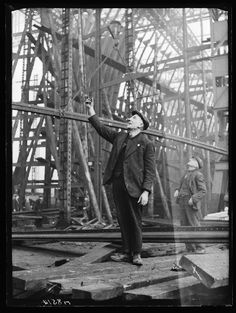 A photograph of workers in the Swan Hunter Shipyard on Tyneside, taken in January 1940 by Bishop Marshall for the Daily Herald.    The photograph shows Harry Hinson, an iron shipwright, standing with a co-worker amongst a framework of a ship's girders. He is shouting directions up to colleagues in the scaffolding. Many warships were built at Swan Hunter during the second world war, including destroyers, destroyer escorts, cruisers and battleships