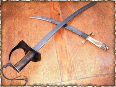 A typical 'cutlass' and a short 'hanger' circa 1700. Both blades were more commonly worn from a waist-belt rather than a shoulder-sling or a 'baldric' by seamen or pirates during 'The Golden Age of Pirates' and are ideally suited to 'hacking and slashing'.  (The items shown are reproductions made by the author using original blades based on museum items )