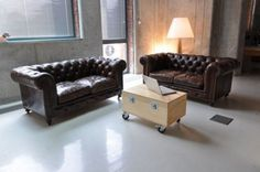 living room office with a brown sofa and a small wooden table unique by using the wheel