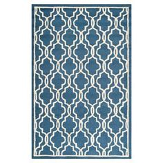 """Anchor your dining room or den decor in elegant style with this hand-tufted wool rug, showcasing a quatrefoil trellis motif in navy and ivory.  Product: RugConstruction Material: WoolColor: Navy and ivoryFeatures:  Hand-tuftedQuatrefoil trellis motifPile Height:0.63"""" Note: Please be aware that actual colors may vary from those shown on your screen. Accent rugs may also not show the entire pattern that the corresponding area rugs have."""