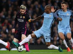 Lionel Messi of Barcelona is tackled by Fernandinho of Manchester City during the UEFA Champions League match between Manchester City FC and FC...
