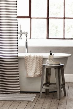 neutral bathroom | white cream gray black + wood | metal stool | creamy chevron towel | gray + white shower curtain | rustic wooden floors