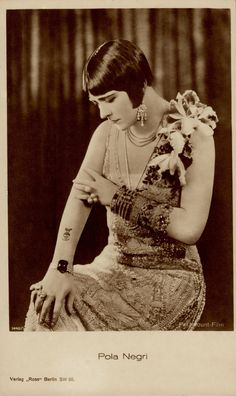"""Skull Tattoo POLA NEGRI (1897-1987) Silent vamp actress.  Pola plays a dangereous & temptuous Italian Countess who shocks a small town. """"I am a woman of the world, not the world's woman"""" she states. She wears a skull tattoo with a butterly atop it. (see detail) Vintage Ross Verlag postcard. From 'WOMAN OF THE WORLD' 1925. (minkshmink postcard collection)"""