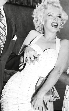 Marilyn Monroe - smiling.  She looks so happy but who's hand is she holding? DiMaggio's?