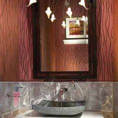 This vanity continues the lesson of creating a bold focal point in a small space. The upper walls of this ultra-feminine retreat are upholstered in padded silk, but the stainless steel backsplash adds a rugged accent.