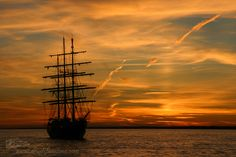 The tall sailing ship Tenacious anchored at Southampton is silhouetted against the dramatic sky at sunset in the English Channel.