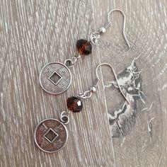 Oorbellen van 8*6mm bruin kristalstenen met metalen Chineese geluksmunten. Van JuudsBoetiek, te bestellen op www.juudsboetiek.nl.