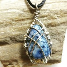 Silver caged dyed blue stone on black rope necklace.