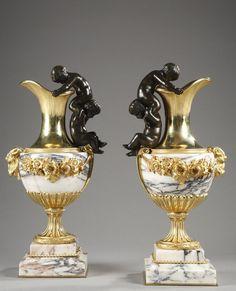 ❤ - Paire d'aiguières en bronze doré et marbre avec des anses formées de chérubins - Une belle paire de vases en forme d'aiguières en marbre et bronze doré avec des anses formées de deux chérubins se faisant la courte échelle. Décor de guirlandes de fleurs sur la panse rejoignant une tête de bouc.  Circa : 1860  Dim: L:19cm, P:13cm, H:35cm.  http://www.artfinding.com/Artwork/%E5%99%A8%E7%9A%BF/Paire-d-aiguieres-en-bronze-dore-et-marbre-avec-des-anses-formees-de-cherubins/8384.html