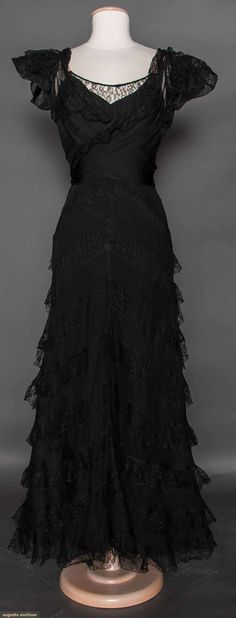 """CHANEL LACE EVENING GOWN, FRANCE, 1933 (front view without jacket) Black silk bias cut underdress w/ nude spaghetti straps, overskirt of bands of black chiffon in chevron pattern alternating w/ black silk lace, bodice attached at B skirt & long chiffon panels cross over bodice to tie CB, ruffled cap sleeves, label """"Chanel"""", tape """"23454"""""""