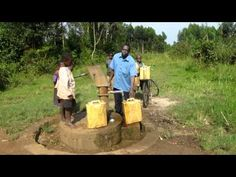 Children collecting water at village pump, Makondo, Uganda