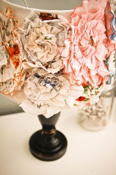 Lampshade with vintage handkerchief rosettes. hang these filled with xmas light from the ceiling.