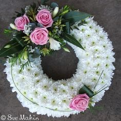 Traditional wreath-shaped tribute, based in white chrysanthemums and dressed with a corsage. You can chose the colour scheme of your corsage below.Size Shown is MediumWe require three working days notice for this piece.Please let us know the time and date of the funeral and the name of the deceased - you can add this in the notes box at checkout.