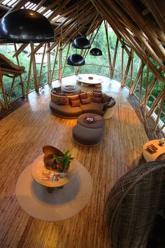 Living room view of the Sharma Springs, Green Village Bali with the open-plan, wall-less rooms on the 4th floor, where the living and dining areas are situated, decorated with playful bamboo and wicker objects, some so unusual-looking it takes a moment to figure out their purpose, with the sides entirely open to the jungle and river valley.