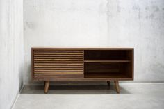 This Solid Black Walnut Media Credenza/ Console/ Sideboard with Slatted Sliding Door will let you store all your entertainment devices in style. There is an option to add an extra slatted door to fully cover the front or leave it as is for an easy access. This functional piece comes with two adjustable shelves and a media opening(s). Beautifully crafted with American Black Walnut.  Please note that all elements in this piece are built with only the best North American Solid Wood and...