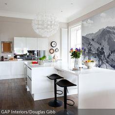 An einer weißen Küchentheke machen sich schwarze Barhocker besonders gut: Sie lenken den Blick des Betrachters auf den Raummittelpunkt und leiten zu der  …